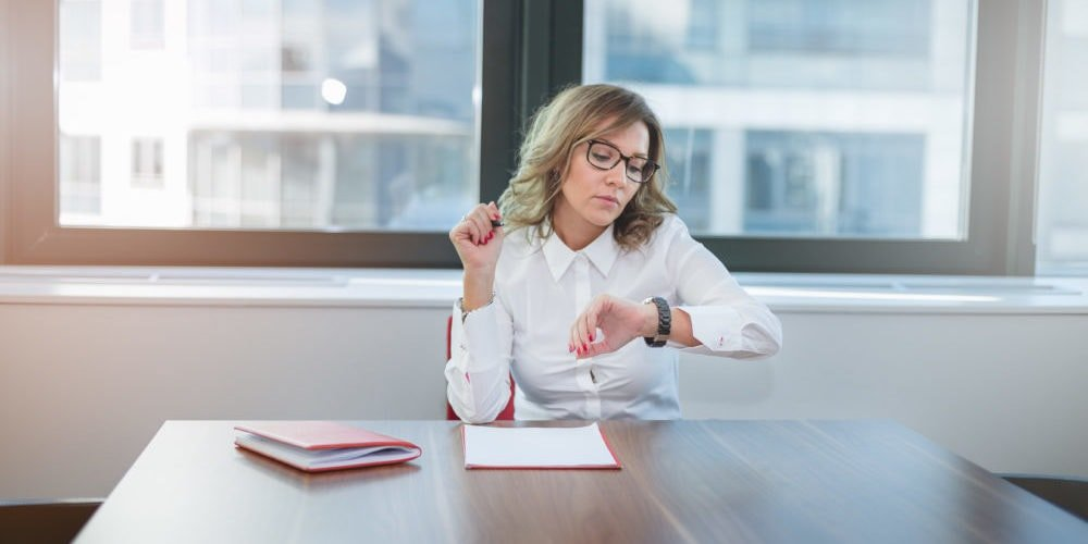 Woman checking watch in meeting room